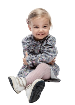 Smiling cute little girl 2 years old in a dress sits cross-legged on the floor. isolated on white background. vertical.