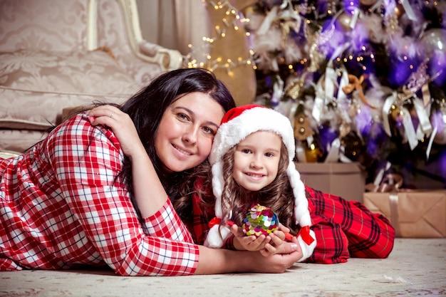 贈り物やクリスマスツリーの近くにサンタの帽子と母親のかわいい女の子の笑顔。