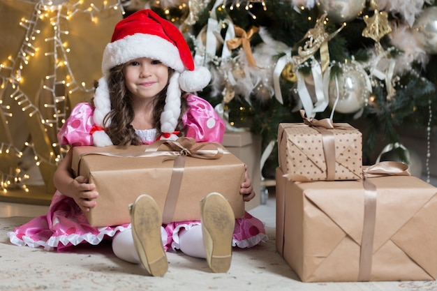 Smiling cute little girl in red santa hat with gift box in her hands near gifts and christmas tree.