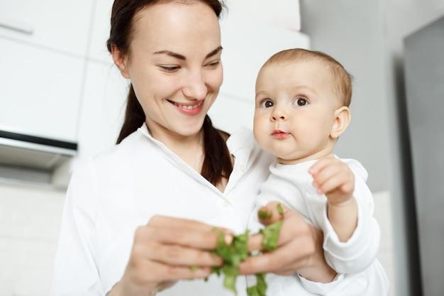Улыбающаяся милая мать кормит ребенка салатом