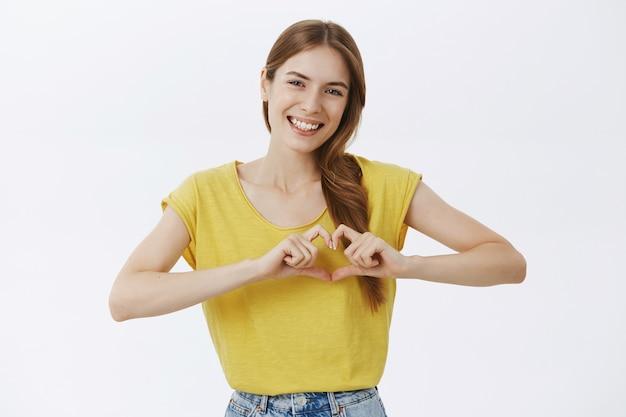 Улыбающаяся милая красивая девушка показывает жест сердца, выражает сочувствие и любовь