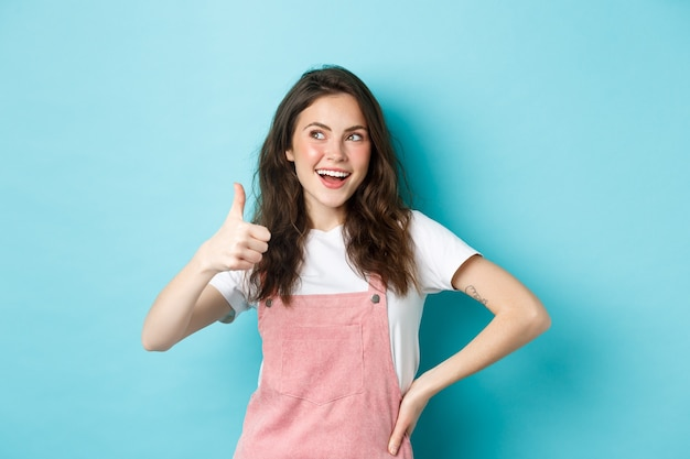 Smiling cute teen girl with beautiful blush and glamour make up, showing thumb up in approval, look at upper left corner banner, recommending store, standing against blue background.