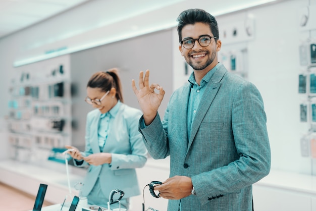 Smiling cute unshaven mixed race man in formal wear holding wristwatch and showing okay sign while looking at camera and standing in tech store. in background woman holding watch.