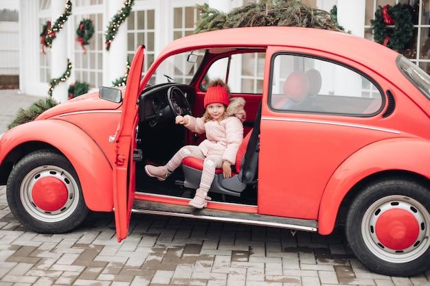 중간 샷 재미 있는 차에 앉아 빨간 모자에 웃는 귀여운 겨울 소녀. 어린 시절을 즐기는 눈송이로 둘러싸인 야외에서 긍정적인 감정을 가진 따뜻한 옷을 입은 행복한 아름다운 여성 아기