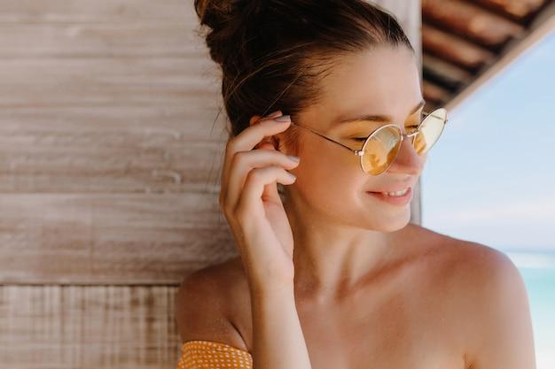여름 촬영을 즐기고 웃는 귀여운 여자. 무두 질된 백인 여자 웃음의 근접 촬영 노란색 선글라스를 착용.
