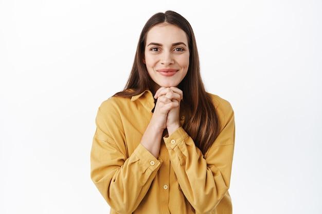 좋은 것을 기대하고, 선물을 기다리거나 기대하는 웃는 귀여운 여성, 희망적인 몸짓으로 손을 잡고 흰 벽 위에 서 있습니다