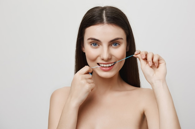 Smiling cute woman flossing teeth with dental floss