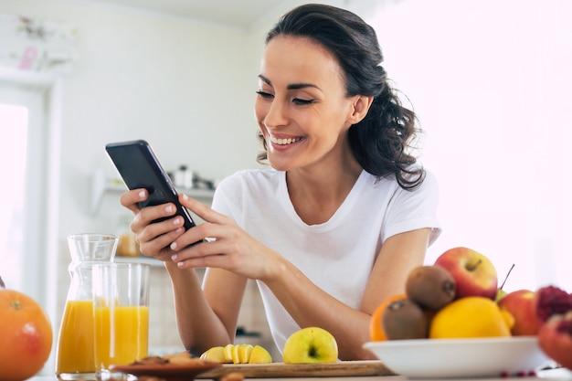 Улыбающаяся милая женщина использует смартфон на кухне дома, готовя фруктовый веганский салат