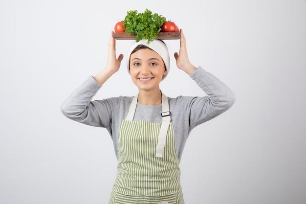 Улыбается милая женщина модель держит деревянную доску со свежими овощами на голове.