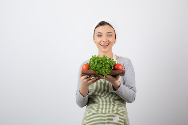 Улыбается милая женщина модель держит деревянную доску со свежими овощами.