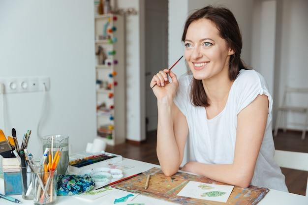 Улыбаясь милая женщина-художник держит кисть и думает за столом в мастерской