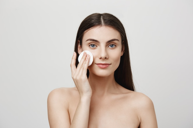 Smiling cute woman take-off makeup with cotton pad