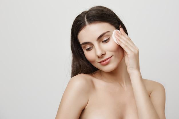 Улыбающаяся милая женщина снимает макияж с ватным диском