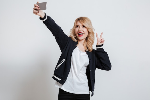 Smiling cute woman taking selfie photo on smartphone