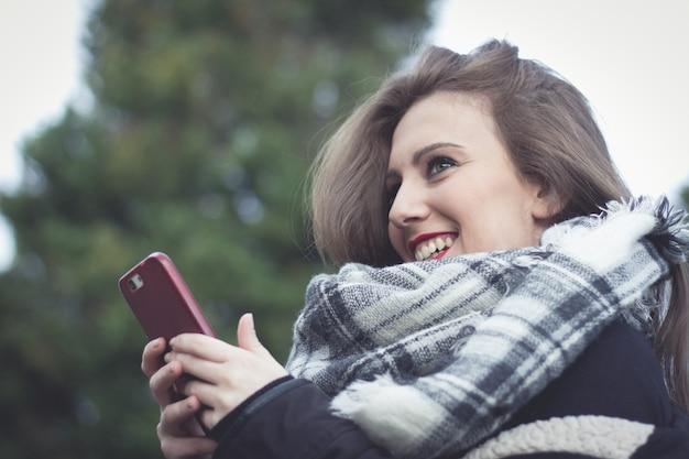 公園でスマートフォンを持って首にスカーフと笑顔のかわいい女性