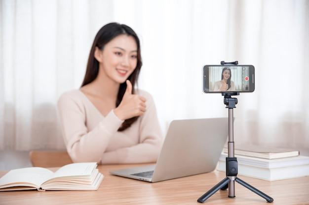 笑顔のかわいい若いアジアの女性ブロガー録画ビデオ
