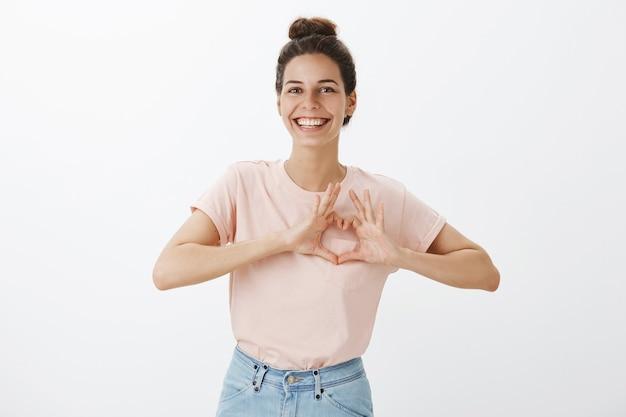 흰 벽에 포즈 웃는 귀여운 젊은 세련 된 여자 무료 사진