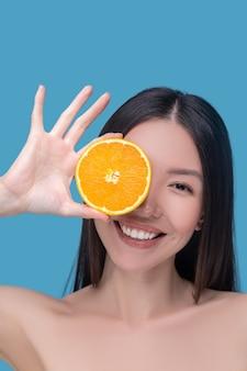 Улыбающаяся милая молодая женщина держит дольку апельсина и прекрасно себя чувствует