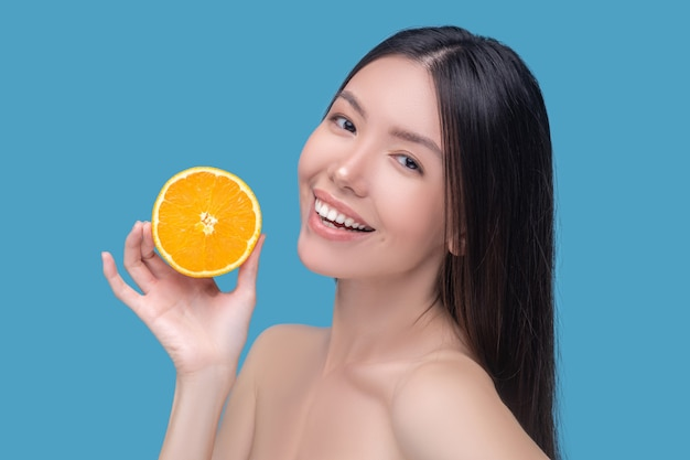 Smiling cute young woman holding a slice of orange and feeling good