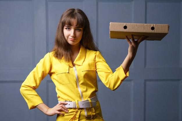 ピザを提供する黄色のジャンプスーツで笑顔のかわいい若い女性。