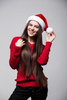 Улыбающаяся милая молодая женщина в шляпе санта-клауса стоит и смотрит на серую стену