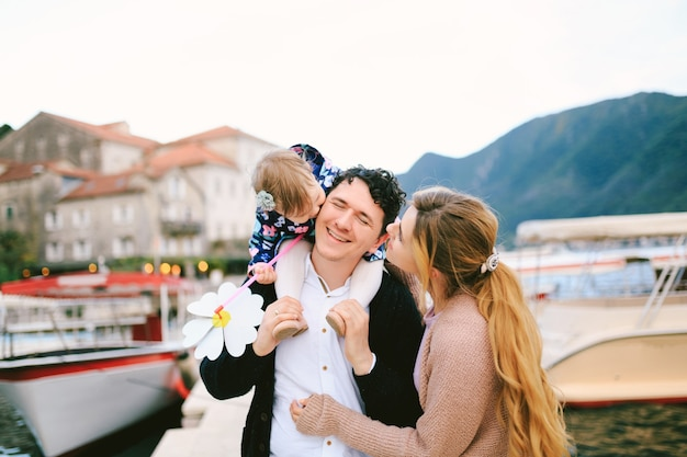 웃는 아빠는 어깨에 딸을 안고 엄마와 딸은 양쪽에서 아빠에게 키스합니다.