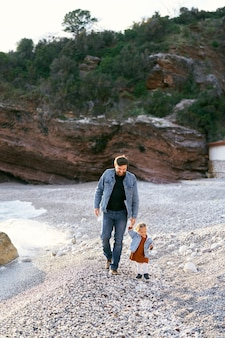 웃는 아빠는 녹색 바위의 배경에 대해 조약돌 해변을 따라 손으로 어린 소녀를 리드