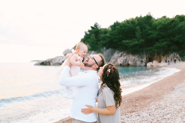 웃는 아빠는 어린 소녀를 팔에 안고 엄마가 뒤에서 아빠를 안고 근처 해변에 서 있습니다