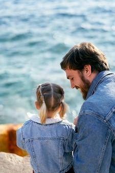 웃는 아빠는 바다 위의 돌에 어린 소녀 옆에 앉아 다시보기 근접 촬영