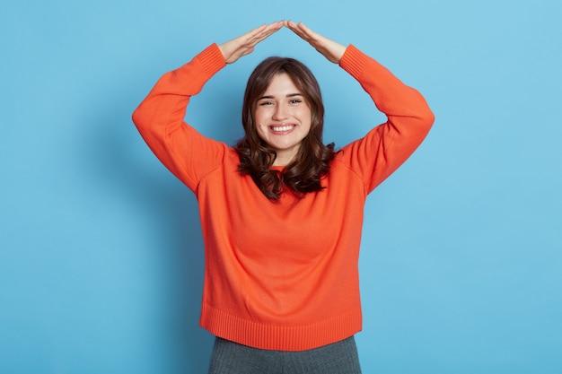 彼女の頭から屋根を作るカジュアルな服を着て、青い壁に隔離された心地よい笑顔でカメラを見ている暗い髪の少女の笑顔。