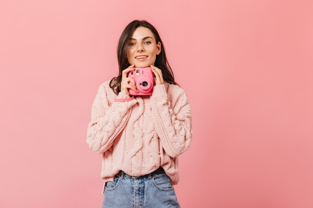 Smiling dark-haired lady in stylish sweater poses with pink camera on isolated background.
