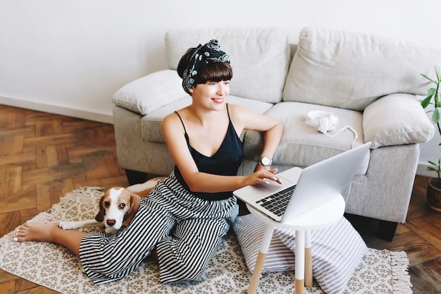 Sorridente signora dai capelli scuri in pantaloni a righe alla moda, lavorando con il computer mentre il suo cane beagle sdraiato accanto