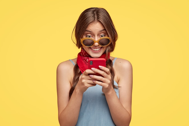 Smiling dark haired woman with cheerful expression, holds red mobile phone, happy to read text message, connected to wireless internet, isolated over yellow wall. people, technology, leisure