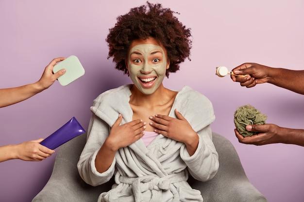 Улыбающаяся темнокожая модель искренне улыбается, наслаждается косметическими процедурами дома.
