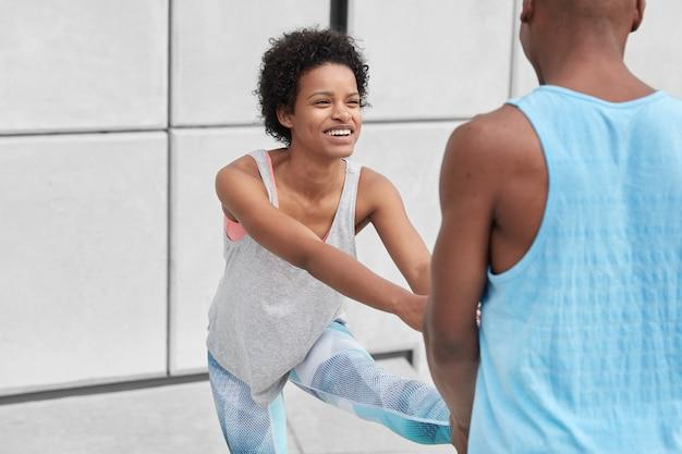 Sorridente donna dalla pelle scura con un sorriso a trentadue denti, ha un'acconciatura afro, indossa un giubbotto, guarda positivamente il suo allenatore, si allena insieme all'aperto, lavora sui muscoli, vuole essere in forma. concetto di stile di vita sano
