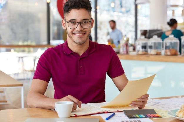 笑顔で満足している起業家は、書類を持って、カジュアルな服を着て、トレーニングワークショップの準備をし、必要な情報を読み、ドキュメントを分析し、カフェのインテリアに対してポーズをとります。労働条件
