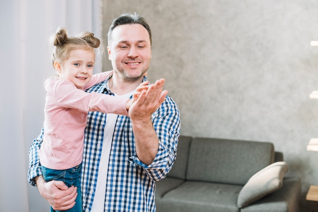 Улыбающаяся дочь хлопает по руке отца в гостиной
