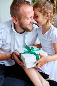 아버지를 축하하고 집에서 생일 선물을주는 딸을 웃고, 어린 소녀는 잘 생긴 아버지에게 아버지의 날 선물 상자를주고 있습니다. 아빠 사랑 해요. 해피 아버지의 날.