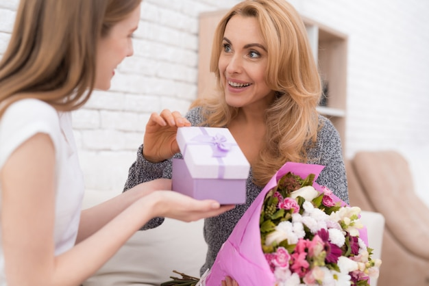 Smiling daughter gives mother flowers and gift.