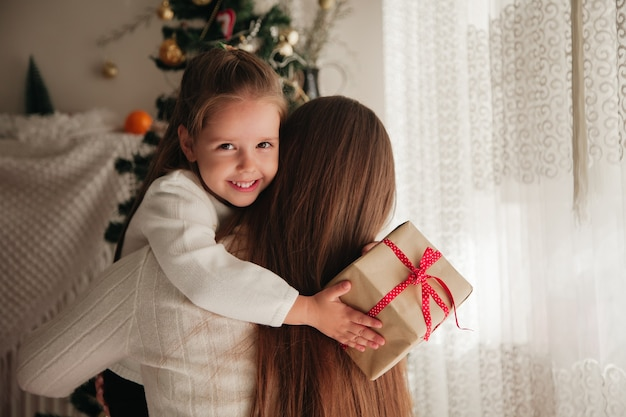 Улыбающаяся дочь обнимает мать с подарком в руках и рождественскими украшениями на заднем плане рождественская семья представляет концепцию
