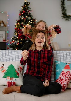Smiling daughter lifts her mother hair holding phone sitting on couch and enjoying christmas time at home