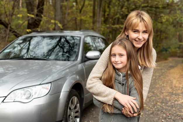 Smiling daughter and mother posing in font of car