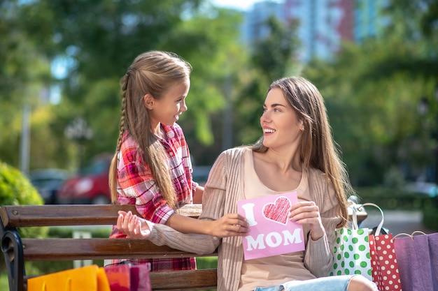 Улыбающаяся дочь, представляя карту для своей мамы, сидя на скамейке в парке
