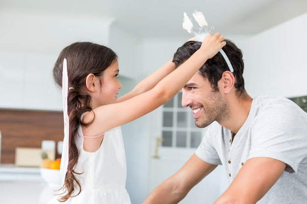 Smiling daughter wearing butterfly headband to father