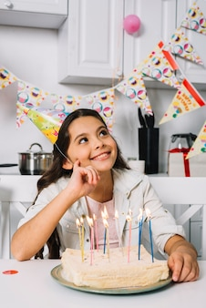 Smiling day dreaming girl sitting in front of birthday cake with illuminated candles