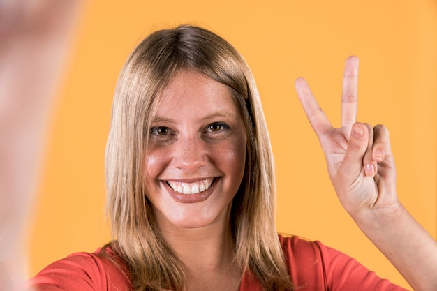 Smiling deaf woman showing victory sign over bright yellow backdrop