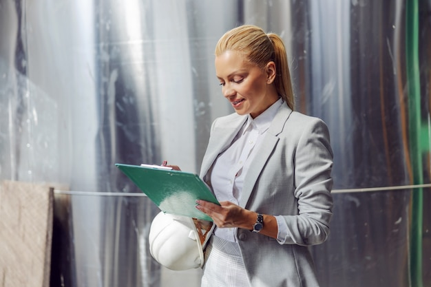 발전소에 서있는 동안 문서를 작성하는 공식적인 마모에 헌신적 인 성공적인 금발 여성 감독자를 웃고 있습니다.