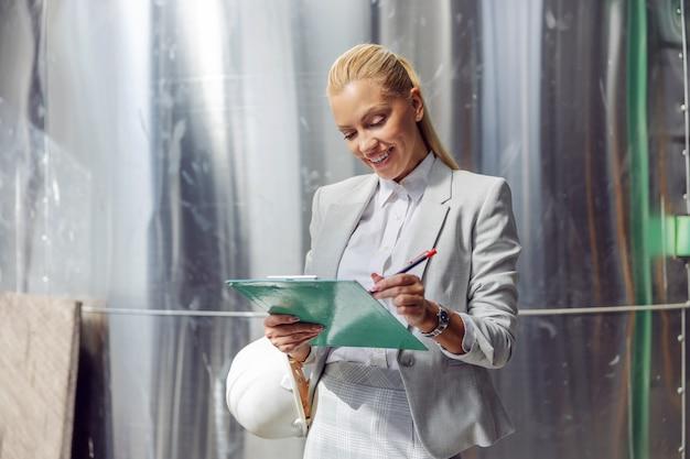발전소에 서있는 동안 문서를 작성하는 공식적인 마모에 헌신적 인 성공적인 금발 여성 감독자 미소 짓기