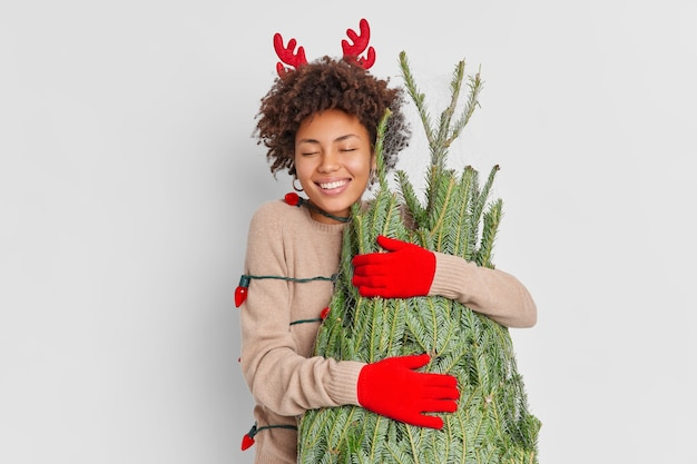 Smiling delighted afro american woman wears reindeer horns and gloves embraces green fir tree with love happy to celebrate new year at home returns from christmas street market wrapped by garland