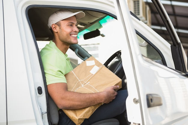 Smiling delivery driver in his van holding parcel